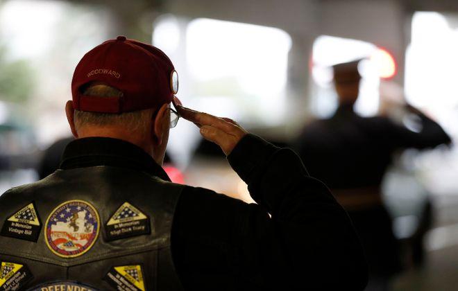 Patriot Guard members salute as the remains of Sgt. Gerald Bernard Raeymacker are placed in a hearse at Buffalo Niagara International Airport. (Mark Mulville/Buffalo News)