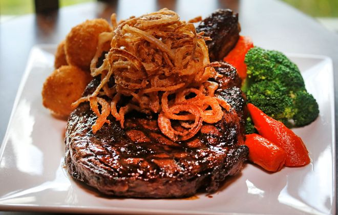The massive cowboy steak with frizzled onions at Rick's on Main. (Robert Kirkham/Buffalo News)