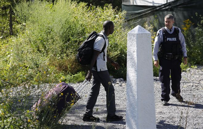 A man seeking asylum is met by an officer from the Royal Canadian Mounted Police as he approaches the border into Canada at the end of Roxham Road. Crossing the border here is only another step in a long journey for refugees seeking new life in Canada. (Derek Gee/Buffalo News)