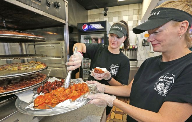 Cooks Krystal Bish, left, and Jean Krafchak tap from a fresh supply of wings from their heated carousel where customers can order single wings a la carte for 97 cents a piece. (Robert Kirkham/Buffalo News)