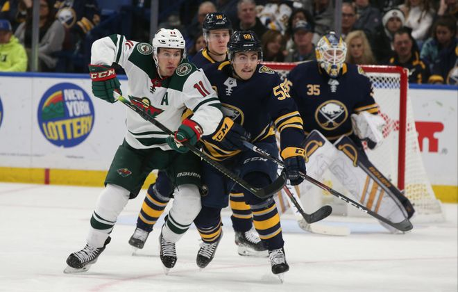 John Gilmour (58) battles Minnesota's Zach Parise (11) for the puck in the first period Tuesday. (James P. McCoy/Buffalo News)