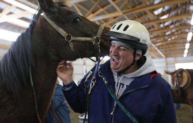 Kevin Degnan  gets a nuzzle from Louie Saturday at the Lothlorien Therapeutic Riding Center in East Aurora during a special outing for the Amputee Support Group of Western New York. (Sharon Cantillon/Buffalo News)