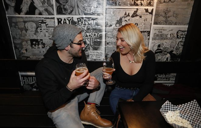 Jeff Christopher, left, and Denise Domagala hang out by the edgy decor of Stone City Saloon. (Sharon Cantillon/Buffalo News)