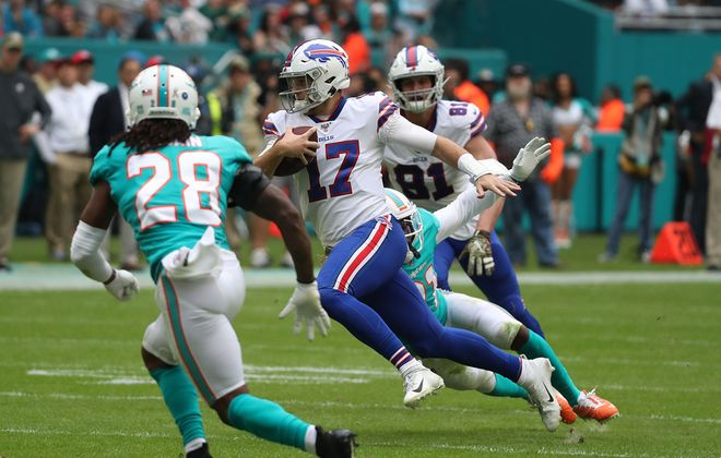 Bills quarterback Josh Allen rushes for a first down against Dolphins strong safety Bobby McCain in the second quarter at Hard Rock Stadium on Sunday, Nov. 17, 2019. (James P. McCoy/Buffalo News)