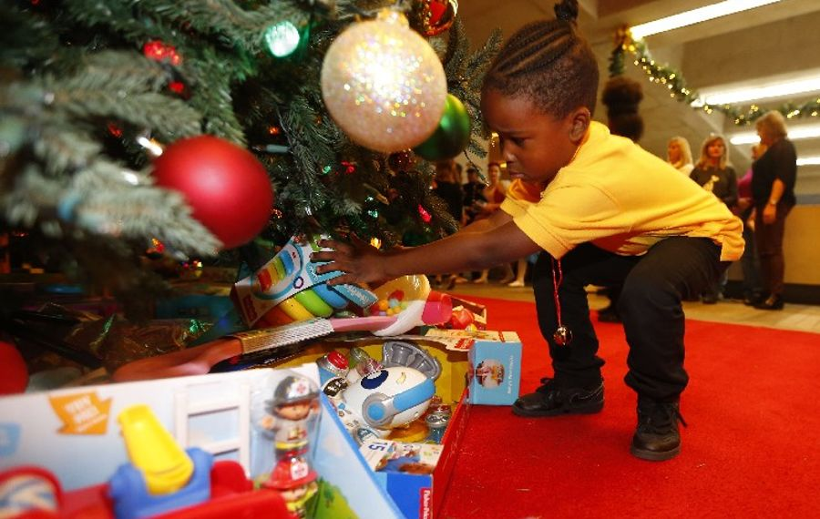 Charter School of Applied Technologies kindergartener Jace Daniels puts a gift under the tree during the kickoff of the annual News Neediest Fund drive in the lobby of The Buffalo News this month. (Mark Mulville/Buffalo News)