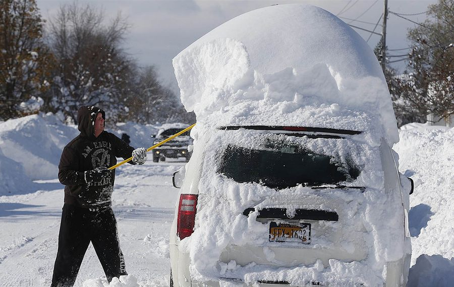 A motorist stopped to remove the cap of snow from atop his van in Depew on Wednesday, Nov. 19, 2014. (Robert Kirkham/Buffalo News)