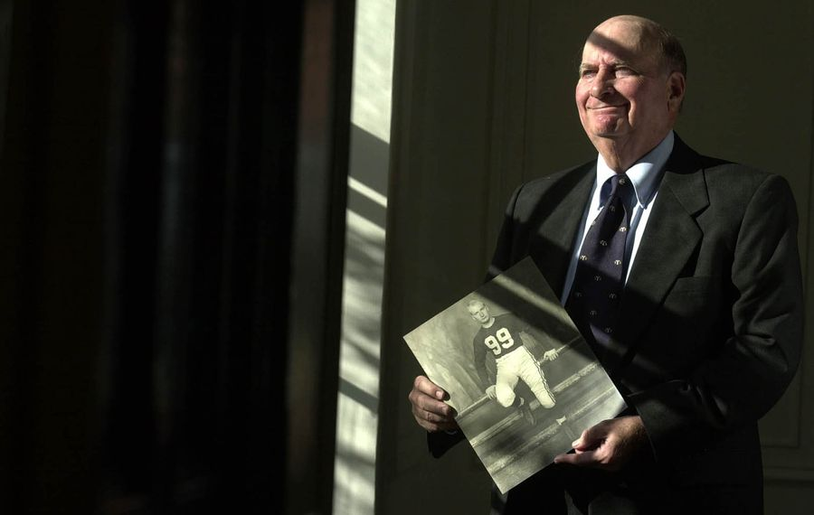 Charles Yeager, photographed at his Buffalo home in 2002, holds a picture from his football days at Yale in the early 1950s. (News file photo)