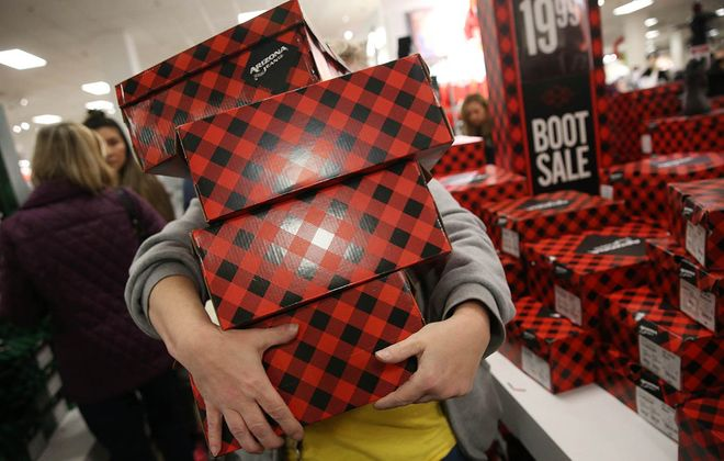 A JCPenney shopper has a hard time managing her four boxes of boots on Black Friday. (Sharon Cantillon/News file photo)