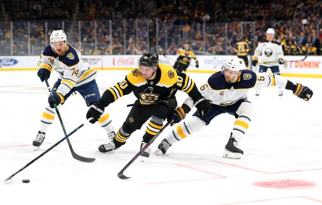 Boston Bruins forward Anders Bjork skates against  Buffalo Sabres defenseman Marco Scandella during the first period at TD Garden on Thursday night. (Getty Images)