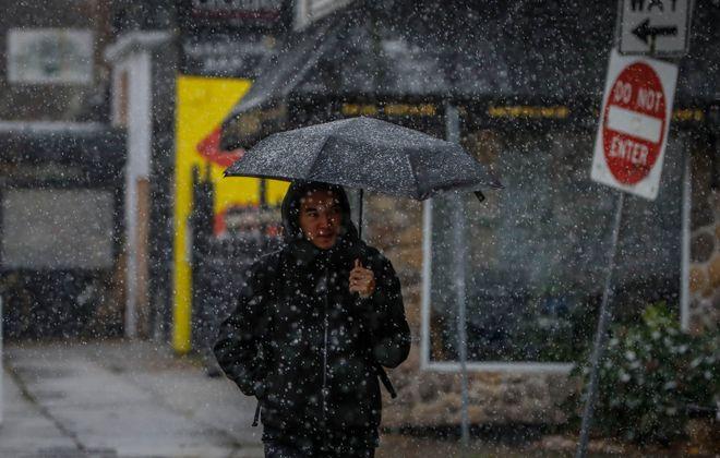 AJ Akimov walks down Elmwood Avenue with an umbrella as the first snow of the season falls in Buffalo. (Derek Gee/Buffalo News)