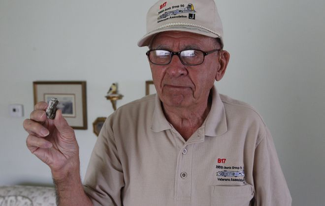 In this 2014 photo, Everett A. Fitchlee of Lockport, then 90, displays the piece of shrapnel removed from his back after he was wounded in a World War II bombing raid over Nazi Germany. (Buffalo News file photo)