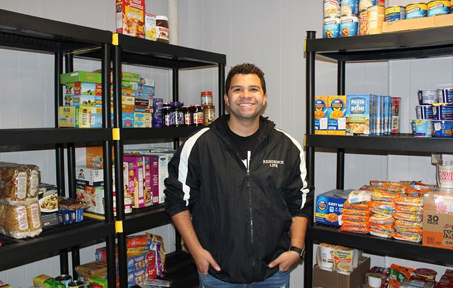Freddie Wade, a community advisor in Niagara University's Office of Residence Life, poses in the university's new food pantry. (Contributed photo)