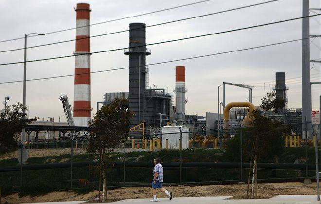A man walks past the Scattergood Generating Station in El Segundo, Calif. The gas-fired power plant operates in one of the communities most affected by pollution in California, according to state data. Los Angeles announced it will abandon plans to renovate three natural gas power plants including Scattergood as part of the state's push toward renewable energy. (Mario Tama/Getty Images)