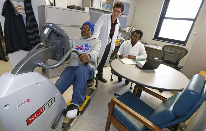 Kenneth Seldeen, standing, research assistant professor of medicine at the University at Buffalo, and Yonas Redae, right, a research associate, monitor the progress of Marine Corps veteran Richard Minor of Buffalo on an exercise bike at the Buffalo Veterans Administration Medical Center on Bailey Avenue earlier this month. (Robert Kirkham/Buffalo News)