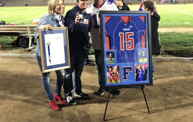 Josh Allen's parents pose with the quarterback's high school jersey as his number was retired at Firebaugh High School (Photo courtesy of Firebaugh High School)