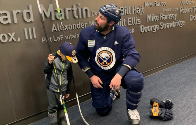 Zach Bogosian spends time with 4-year-old Andre Sanders after practice Friday (Lance Lysowski / Buffalo News)