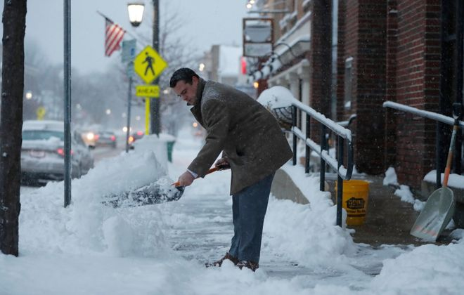 Nick DeMarco clears the sidewalk in front of Attea & Attea, P.C. in Hamburg on Tuesday morning. (Mark Mulville/Buffalo News)