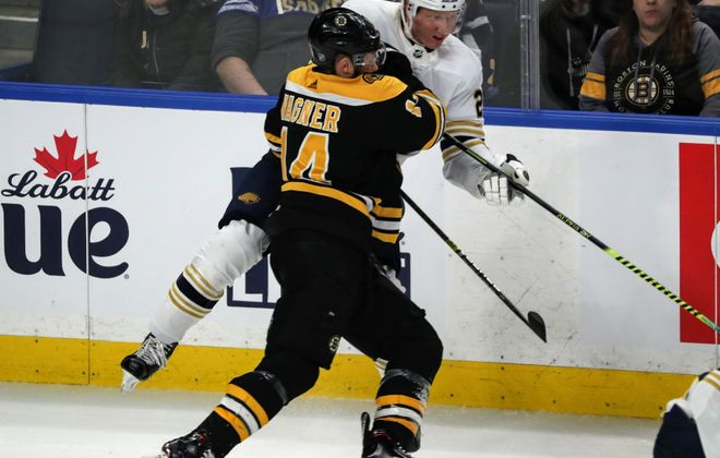 Rasmus Dahlin gets hammered into the boards by the Bruins' Chris Wagner during Friday's game at KeyBank Center. (James P. McCoy/Buffalo News)