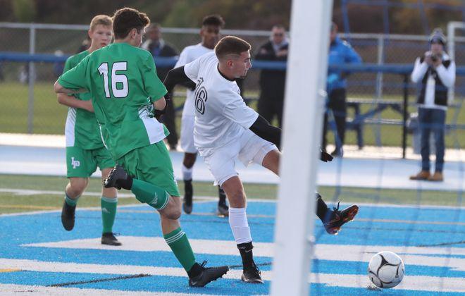 Niagara Wheatfield's Jacob Vallas takes a shot on net around Lewiston-Porter defender Cole Accetta. (James P. McCoy/News file photo)