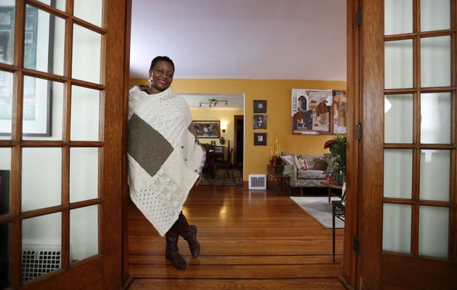 Renata Toney at her Buffalo home. A work by Dennis Maher hangs above the living room sofa behind her.  (Mark Mulville/Buffalo News)