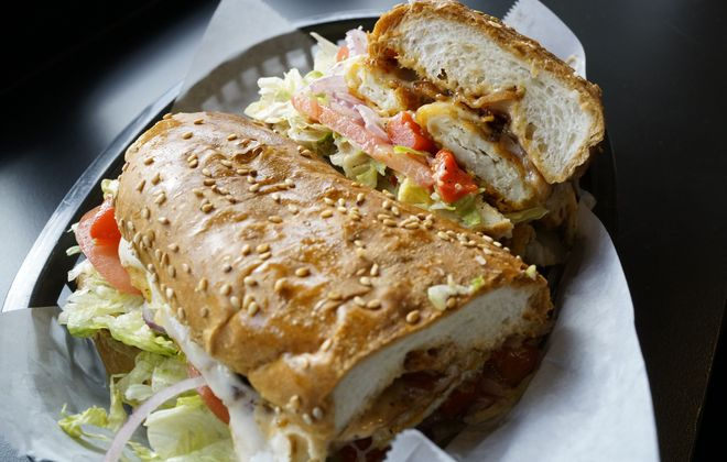 The Big Bird, with grilled chicken tenders, bacon, melted mozzarella cheese, lettuce, tomato, red onion, red sweet peppers and chipotle mayo, one of the signature Sangwiches at Marco's Italian Deli. (Derek Gee/Buffalo News)