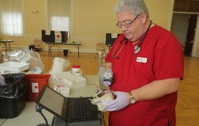 Paul Ernewein, a Red Cross donor specialist, works at cataloging donated blood at the  University at Buffalo South Campus in Buffalo. (John Hickey/Buffalo News)