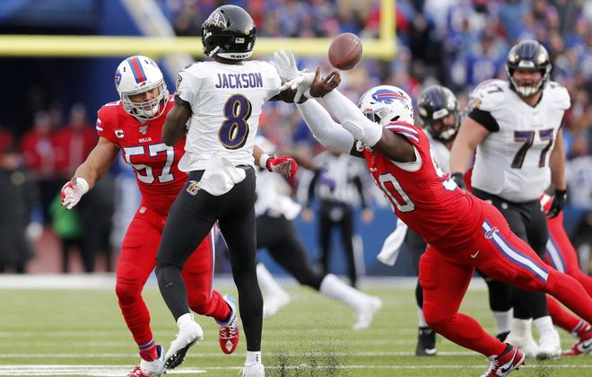 Buffalo Bills defensive end Shaq Lawson (90) knocks the arm of Baltimore Ravens quarterback Lamar Jackson (8) as Buffalo Bills outside linebacker Lorenzo Alexander (57) pressures in the third quarter at New Era Field in Orchard Park Sunday, December 8, 2019.      (Mark Mulville/Buffalo News)