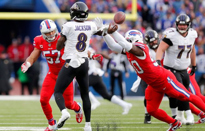 Buffalo Bills defensive end Shaq Lawson (90) knocks the arm of Baltimore Ravens quarterback Lamar Jackson (8) as Buffalo Bills outside linebacker Lorenzo Alexander (57) pressures in the third quarter at New Era Field in Orchard Park Sunday, December 8, 2019.      (Mark Mulville/Buffalo News)