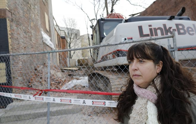 Susan Adamucci, owner of Two Wheels Bakery, looks into the pit where the building that housed her business since 2018 was demolished after the roof collapse rendered the 1860's-era building unsafe, Sunday, Dec. 8, 2019. She estimates upward of $90,000 of restaurant equipment was lost in the demo, a major setback for her business, which is continuing with the help of friends. (Derek Gee/Buffalo News)