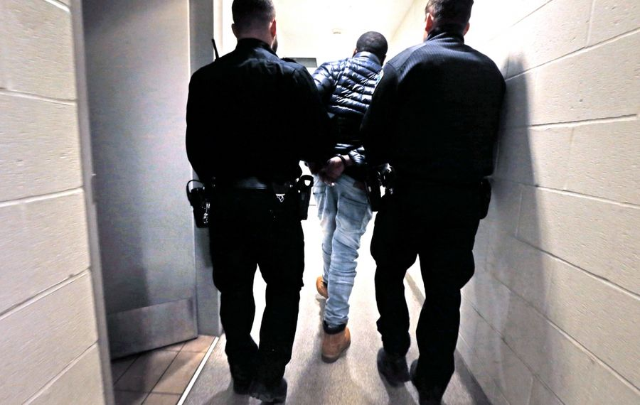 Buffalo police officers escort a suspect to a holding cell at Central Booking. (Robert Kirkham/News file photo)
