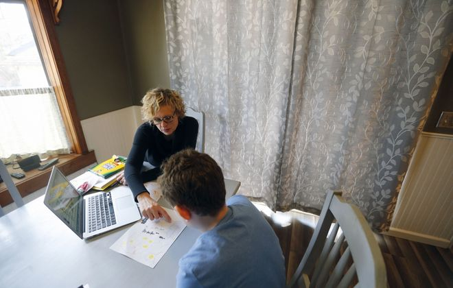 Susan Walterich works on a lesson with her son, Brendan, in their Hamburg home. She began home schooling him this fall as an alternative after the state cracked down on students who hadn't gotten their required vaccinations. (Mark Mulville/Buffalo News)
