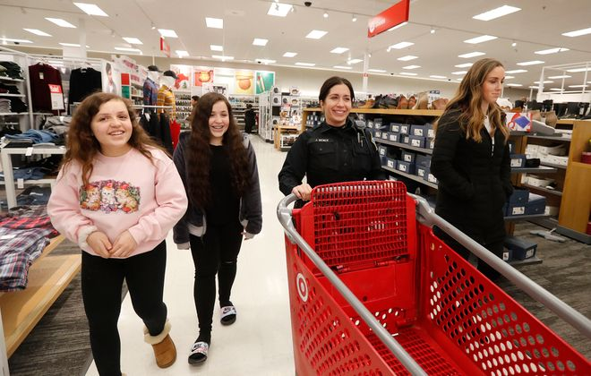 Haley Jacobsen and her sister Alyssa Jacobsen, left, shop at Target with Buffalo Police Officer Joelle Bence on Wednesday, Dec. 18, 2019. (Mark Mulville/Buffalo News)