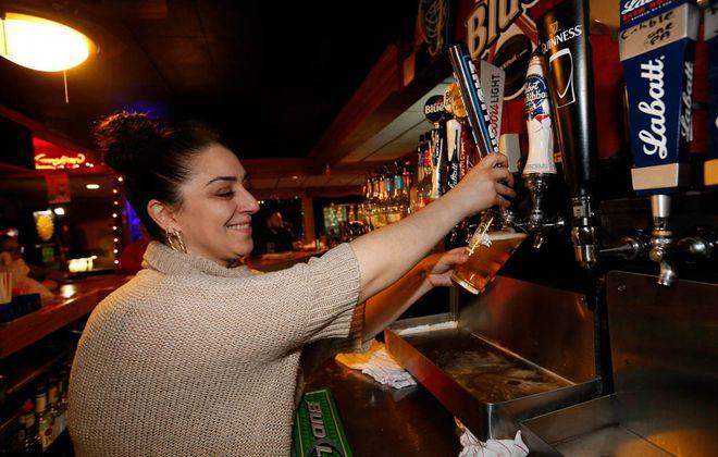 Bartender Dimitra Sergakis pours a customer a Bud Light inside Witter's Sports Bar. (Sharon Cantillon/Buffalo News)