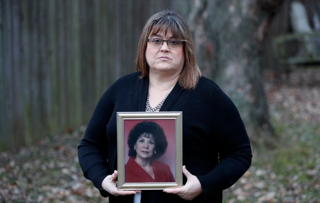 """The restitution order for the fraud committed by Amherst financial adviser James D. Tetrault """"isn't worth the paper it was printed on,"""" says Colleen Drake of Cheektowaga, holding a portrait of her late mother,  Moynette Kauffman, who also lost money.  (Mark Mulville/Buffalo News)"""