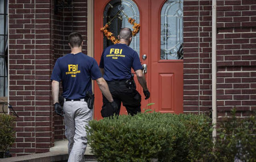 FBI agents walk back into the home of UAW president Gary Jones during a raid in August. Jones has taken a leave of absence from his post. (TNS)