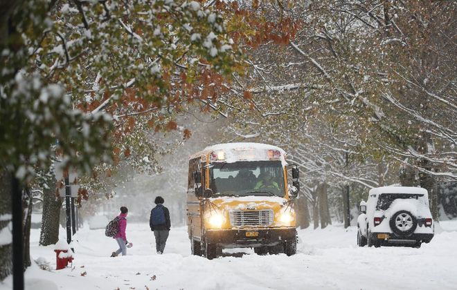 Students board a school bus in North Buffalo last month. Some children are required to walk to school in harsh weather or through dangerous neighborhoods. The state is considering a plan to alleviate that problem. (Sharon Cantillon/Buffalo News)
