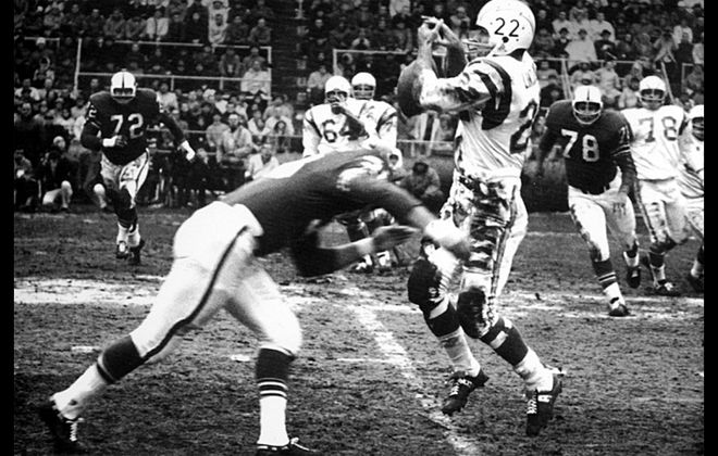 "Bills linebacker Mike Stratton closes in on San Diego Chargers running back Keith Lincoln in the 1964 AFL Championship Game for what would be called the ""Hit Heard 'Round the World."""