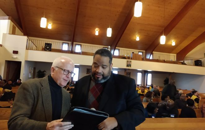 The Rev. M. Bruce McKay, left, and Bishop Dwayne Royster review strategies for building a new City of Niagara Falls at a community meeting on Saturday in Niagara Falls. (Lou Michel/Buffalo News)