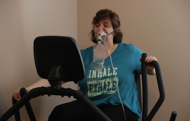 Melissa King 47, who has pulmonary fibrosie, has a recumbent stepper in the den of her home in the Town of Niagara but feels better, and safer, about giving her all during fitness classes at the Kenmore Mercy Hospital Pulmonary Maintenance Program, which is scheduled to close next month. (Sharon Cantillon/Buffalo News)