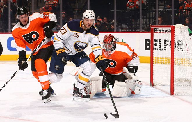 Sabres winger Sam Reinhart and Flyers defenseman Justin Braun battle for the puck in front of goalie Carter Hart (Getty Images).