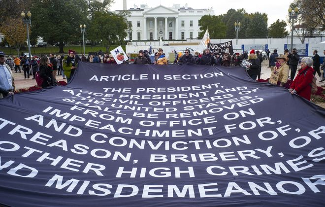 A group of demonstrators, in front of the White House on Nov. 6, 2019, hold a large banner with the text from the U.S. Constitution that outlines the impeachment of a president. (Stephen Crowley/Special to The News)