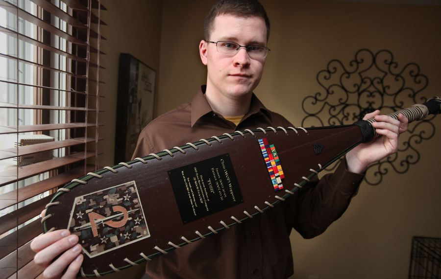 Former Marine Corps Sgt. Chris Wopperer holds a ceremonial paddle presented to him by the soldiers of the Marine Corps 2nd force Recon Platoon, at the end of his tour of duty, in his Amherst home, Monday, Feb. 28, 2011. (News file photo)