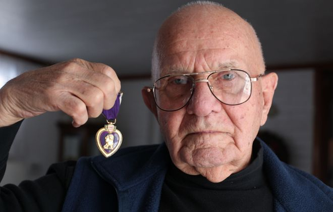 James Wagner holds a purple heart he earned while serving with the U.S. Marines in the Pacific during World War II on Monday, Jan. 24, 2011. (News file photo)