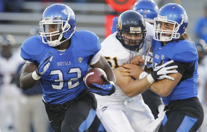 Mark Mulville / Buffalo News  UB's Branden Oliver picks up yardage the first half before leaving with a leg injury.
