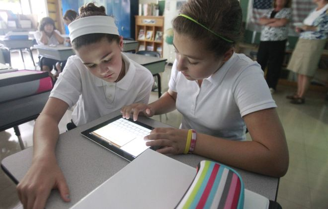John Hickey/Buffalo News    Danielle Hore , 12, left, and Gianna Dignitti ,12, type on an iPad Thursday in Michael Kerwin's class at Nativity of Our Lord School  in Orchard Park.