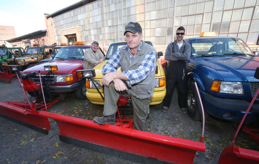 Peter Militello, center, owner of Militello Landscaping and Snowplowing in Buffalo, stands by some of his company's smaller vehicles with Eric Fagan, left, and Dave Guizzotti, right.