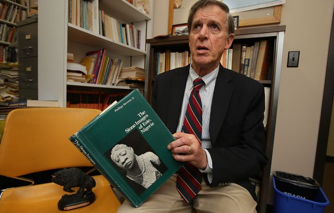 Phillips Stevens Jr., an associate professor of Anthropology, holds a book of photos of the fascinating Nigerian stone carvings he helped to document and preserve. (Buffalo News file photo)