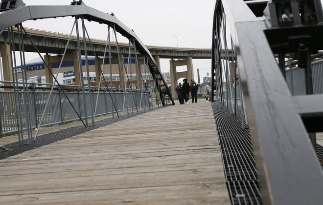 Tourists wander Friday over the bridge across the Commercial Slip at Canalside.  The ironwork on the bowstring bridge has begun showing traces of rust, and some of the planking has warped, detracting from the structure's beauty.
