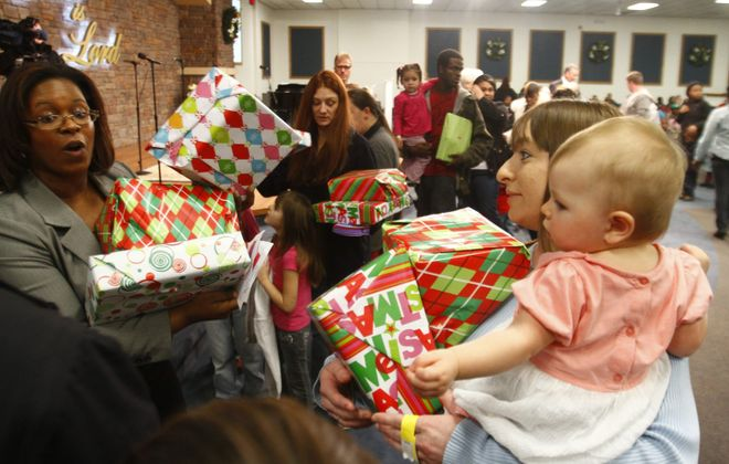 Vanessa DeSosa holds gifts and her daughter Heaven ,1, at New Creation Fellowship Church.