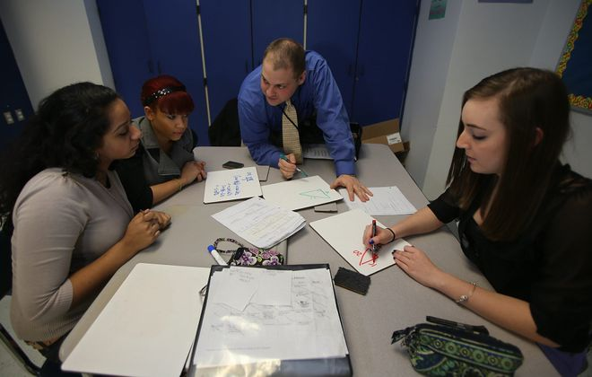 Ed Ventry teaches algebra 2 and trigonometry at Niagara Falls High School to class including, from left, Ashlee Akhter, Sierra Watson  and Jessica Evans. With new program, work that used to be done in school is done at home and vice versa, leading to better efficiency.
